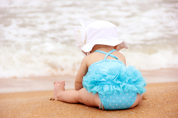 Baby sitting at beach wearing the beach essentials.