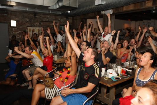 Crowd cheering while watching soccer world cup final at Brooklyn Beer Garden Black Forest