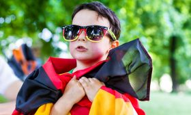 boy with germany flag and sunglasses watching soccer